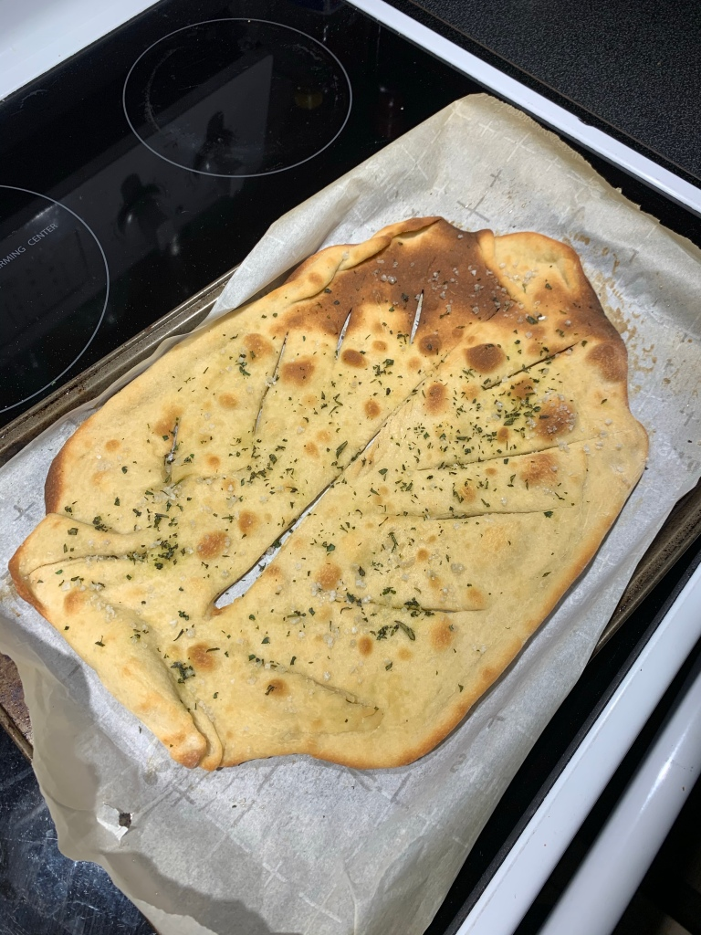 A  flat bread with seasoning on top. Slits have been cut to make it look like a leaf. It is very dark brown in the top left.