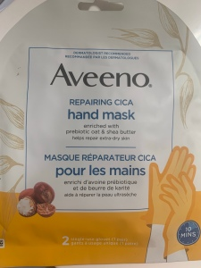 A photograph  of the Aveeno hand mask package. The package is white with light orange writing.
