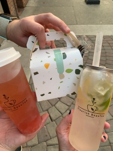 A photograph of two drinks in clear plastic containers bearing the name Flourish BeauTea.  One tea is yellow with lime and lemons, and the other drink is a soft orange red. There is a to-go box with green and yellow design swoops.