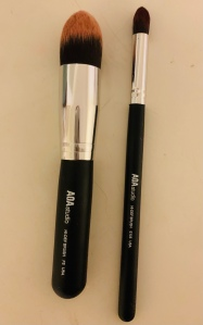 A top down image of two makeup brushes. They have black handles and bristles shaped into a pointed oval.
