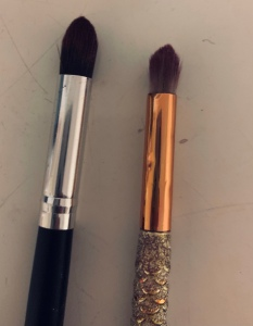 Two brushes, taken from a top down angle. The brush on the left is new, and the one one the right  is showing visible signs of wear and tear.