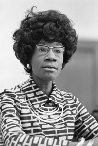 An image of Shirley Chisholm. It is a black and white image, she wears a collared top with a block pattern and rimmed glasses.