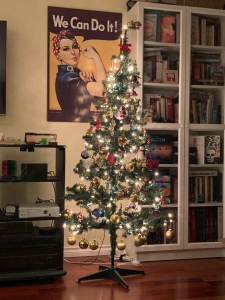 A Christmas tree festooned with white lights and many ornaments.