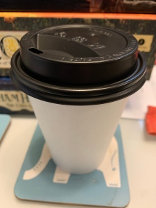 An image of a white to go cup with a black lid
