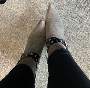 A picture of grey boots with a black strap