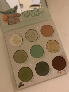 A nine pan eyeshadow palette with green and brown shadows. There is a mirror and an illustrated image of the child from the Mandalorian - it says  cutest in the galaxy.