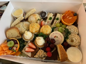 A top down image of a white box filled with dainty fruit cups, pastries, pinwheel sandwiches, and other baked goods.