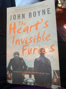 A picture of the book cover. Heart's invisible furies is in orange,  overlaid on an image of muted tones.  There are two men in jackets facing away from the camera.