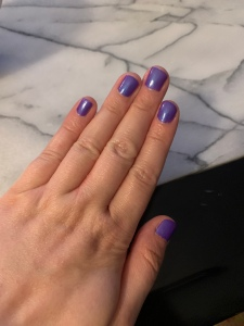 A top down image of my hands. I am wearing a bright purple nail polish.