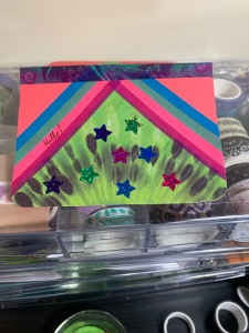 A photograph of a brightly coloured card with stripes of washi tape.