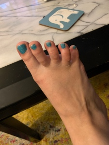 A picture of my foot with teal polish and sparkle on top.