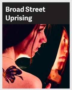 An image of a girl  with a butterfly tattoo on her shoulder. She is holding a bloody knife. The words Broad Street Uprising is above her.